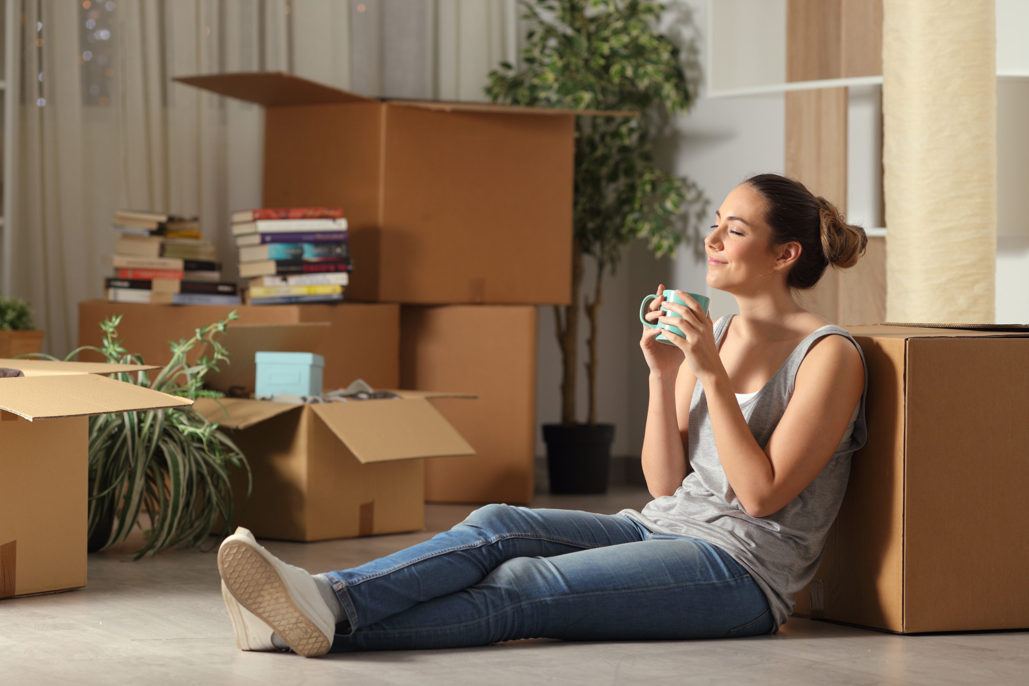 woman sitting on floor in home with moving boxes
